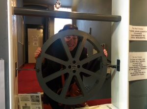 posing by the model of the Reel Cinema's logo built in as a feature of the interior by the box office